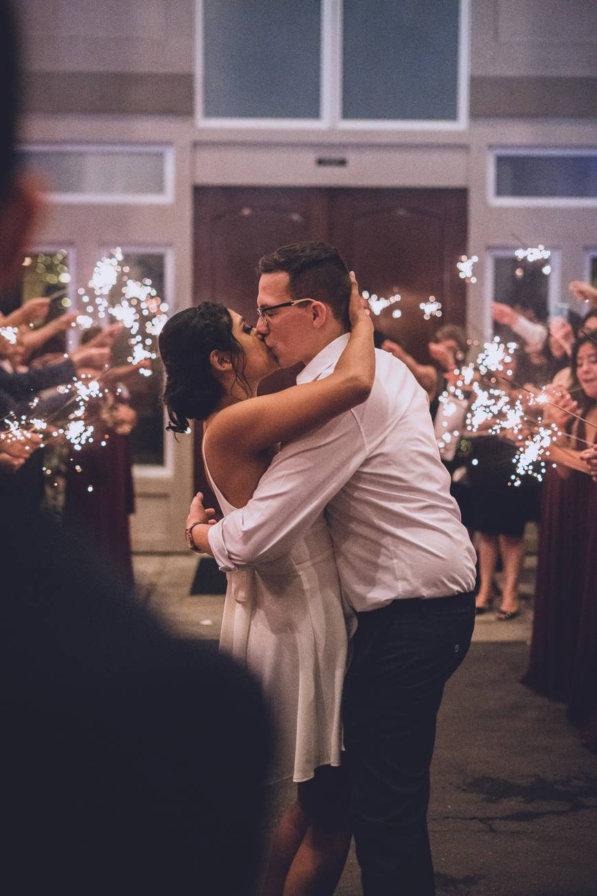 man and woman kissing near people with sparkles